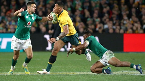Australia's Israel Folau, center, attempts to run through Ireland's Johnny Sexton, left, and Bundee Aki during their rugby union test match in Sydney, Saturday, June 23, 2018. (AP Photo/Rick Rycroft)