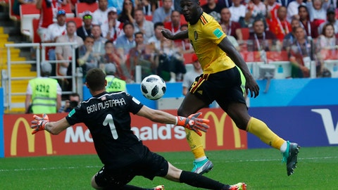 Belgium's Romelu Lukaku , right, scores their side's third goal past Tunisia goalkeeper Farouk Ben Mustapha during the group G match between Belgium and Tunisia at the 2018 soccer World Cup in the Spartak Stadium in Moscow, Russia, Saturday, June 23, 2018. (AP Photo/Hassan Ammar)