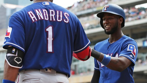 Texas Rangers' Jurickson Profar, right, smiles as Elvis Andrus congratulates him after Profar scored on a two-run single by Delino DeShields off Minnesota Twins pitcher Jake Odorizzi in the second inning of a baseball game Saturday, June 23, 2018, in Minneapolis. (AP Photo/Jim Mone)