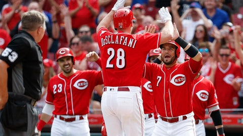 Cincinnati Reds' Anthony DeSclafani (28) celebrates with Eugenio Suarez (7) after hitting a grand slam off Chicago Cubs relief pitcher Brian Duensing in the third inning of a baseball game, Saturday, June 23, 2018, in Cincinnati. (AP Photo/John Minchillo)