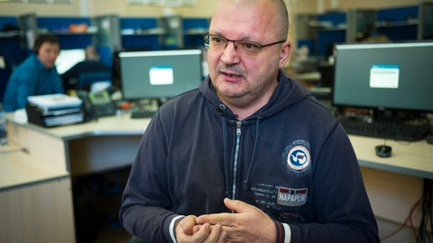 """In this photo taken on Monday, May 21, 2018, Oleg Semyonov, a former senior member of the Spartak Moscow fan scene who now manages a legal advice helpline for fans, speaks to the Associated Press in Moscow, Russia. Oleg Semyonov is Russia's World Cup fixer. The call center he runs for fans is a hubbub of talk in several languages, resolving taxi scams, ticket fraud and even medical emergencies. """"Fans from Tunisia, Morocco, Asian countries celebrate so emotionally on Manezh or Nikolskaya,"""" he says, naming two locations where fans gather in central Moscow, """"that they injure themselves. Tearing a meniscus or something like that. We help them get an ambulance and emergency care in hospital."""" (AP Photo/Alexander Zemlianichenko)"""