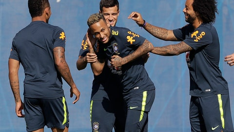 Brazil's Marcelo, right, and Philippe Coutinho, back, joke with teammate Neymar, during a training session, in Sochi, Russia, Sunday, June 24, 2018. Brazil will face Serbia on June 27 in the group E for the soccer World Cup. (AP Photo/Andre Penner)