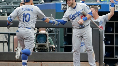 Los Angeles Dodgers' Justin Turner, left, is greeted by Max Muncy after hitting a solo home run during the 11th inning of a baseball game against the New York Mets at Citi Field, Sunday, June 24, 2018, in New York. (AP Photo/Seth Wenig)