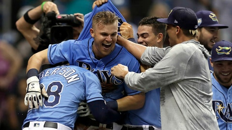 Tampa Bay Rays' Jake Bauers, center, celebrates with teammates after his walkoff home run off New York Yankees relief pitcher Chasen Shreve during the 12th inning of a baseball game Sunday, June 24, 2018, in St. Petersburg, Fla. (AP Photo/Chris O'Meara)
