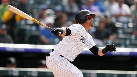 Colorado Rockies' Gerardo Parra follows the flight of his solo home run off Miami Marlins relief pitcher Drew Rucinski in the fourth inning of a baseball game Sunday, June 24, 2018, in Denver. (AP Photo/David Zalubowski)