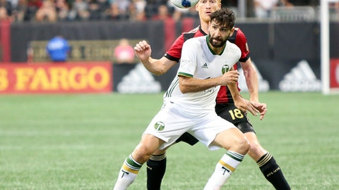 Portland Timbers midfielder Diego Valeri (8) is defended by Atlanta United defender Jeff Larentowicz (18) in the second half of an MLS soccer match Sunday, June 24, 2018, in Atlanta, Ga. The match ended in a 1-1 draw. (AP Photo/Brett Davis)
