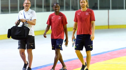 Switzerland's midfielder Gelson Fernandes, center, and Switzerland's defender Michael Lang, right, arrives with Marco Von Ah, left, media officer of the Swiss Football Federation before a press conference after a closed training session of the Switzerland's national soccer team at the Torpedo Stadium, in Togliatti, Russia, Monday, June 25, 2018. (Laurent Gillieron/Keystone via AP)