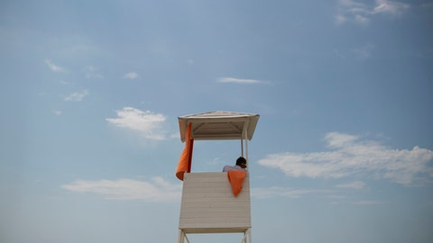 FILE - In this Friday, June 15, 2018 filer, a lifeguard looks out from a watchtower on the beach at the Black Sea during the 2018 soccer World Cup in Sochi, Russia. Sochi in the summer is a whole lot different than what fans saw during the Winter Olympics. The snow is replaced by lots of sun as Russia's summertime playground explodes in a scene more akin to Southern California or Miami Beach than Siberia. World Cup fans have been taking advantage of the beaches, waterparks and other warm-weather activities, and teams have been eager to train there. (AP Photo/Francisco Seco, File)