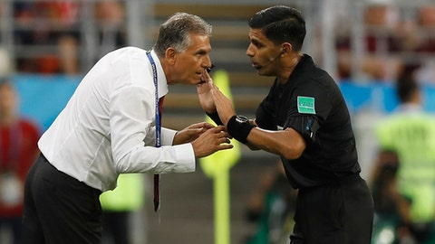 Referee Enrique Caceres from Paraguay, right, speaks to Iran head coach Carlos Queiroz during the group B match between Iran and Portugal at the 2018 soccer World Cup at the Mordovia Arena in Saransk, Russia, Monday, June 25, 2018. (AP Photo/Francisco Seco)