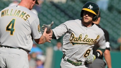 Oakland Athletics' Jed Lowrie is greeted by third base coach Matt Williams after a solo home run during the ninth inning of a baseball game against the Detroit Tigers, Monday, June 25, 2018, in Detroit. (AP Photo/Carlos Osorio)