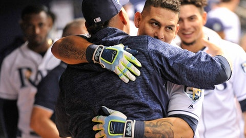 Tampa Bay Rays' Jesus Sucre, center, hugs Wilson Ramos in the dugout after Ramos' two-run homer off Washington Nationals reliever Tim Collins during the sixth inning of a baseball game Monday, June 25, 2018, in St. Petersburg, Fla. (AP Photo/Steve Nesius)