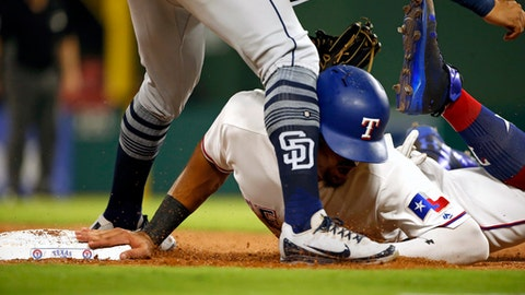 Texas Rangers Ronald Guzman collides with San Diego Padres third baseman Christian Villanueva while diving back safely to third base during the sixth inning of a baseball game Monday, June 25, 2018, in Arlington, Texas. Guzman left the game following the play. (AP Photo/Ron Jenkins)