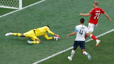 France goalkeeper Steve Mandanda, left, jumps to stop the ball ahead of Denmark's Andreas Cornelius, right, during the group C match between Denmark and France at the 2018 soccer World Cup at the Luzhniki Stadium in Moscow, Russia, Tuesday, June 26, 2018. (AP Photo/Victor R. Caivano)