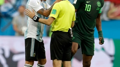 Argentina's Marcos Rojo, left, touches the referee Cuneyt Cakir during the group D match between Argentina and Nigeria, at the 2018 soccer World Cup in the St. Petersburg Stadium in St. Petersburg, Russia, Tuesday, June 26, 2018. (AP Photo/Petr David Josek)