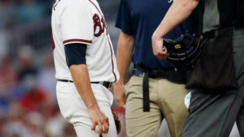 Atlanta Braves starting pitcher Anibal Sanchez (19) talks with a member of the training staff and an umpire before leaving during the fifth inning of the team's baseball game against the Cincinnati Reds on Tuesday, June 26, 2018, in Atlanta. (AP Photo/John Bazemore)