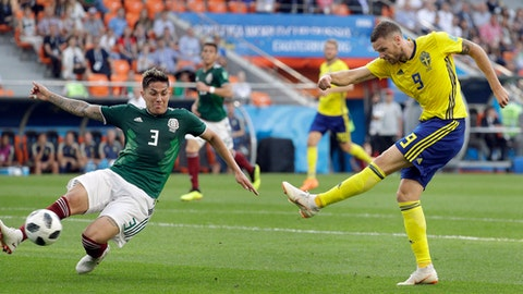 Mexico's Carlos Salcedo, left, and Sweden's Marcus Berg, right, challenge for the ball during the group F match between Mexico and Sweden, at the 2018 soccer World Cup in the Yekaterinburg Arena in Yekaterinburg , Russia, Wednesday, June 27, 2018. (AP Photo/Gregorio Borgia)