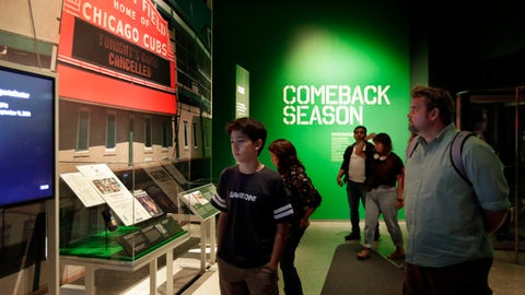 "Visitors to the National September 11 Memorial & Museum attend the ""Comeback Season: Sports After 9/11"" exhibit in New York, Wednesday, June 27, 2018. The new exhibit highlights the impact of sports after the 2001 attacks, including the Mets' win in New York's first major sporting event after 9/11. (AP Photo/Richard Drew)"