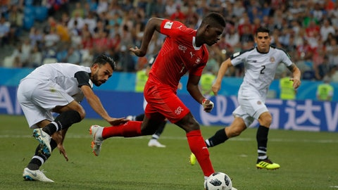 Switzerland's Breel Embolo, right, runs with the ball past Costa Rica's Bryan Ruiz, left, during the group E match between Switzerland and Costa Rica at the 2018 soccer World Cup in the Nizhny Novgorod Stadium in Nizhny Novgorod , Russia, Wednesday, June 27, 2018. (AP Photo/Vadim Ghirda)