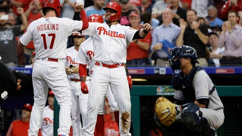 Philadelphia Phillies' Rhys Hoskins, left, and Jorge Alfaro, center, celebrate next to New York Yankees catcher Kyle Higashioka, right, after Hoskins' three-run home run off starting pitcher Luis Cessa during the second inning of a baseball game Wednesday, June 27, 2018, in Philadelphia. (AP Photo/Matt Slocum)