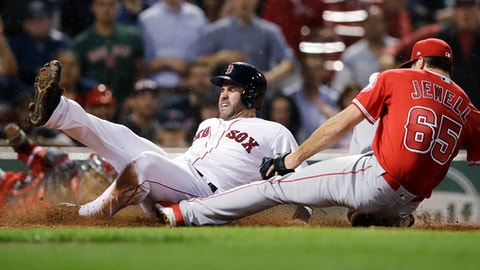 Boston Red Sox's J.D. Martinez, left, scores on a wild pitch as Los Angeles Angels' pitcher Jake Jewell (65) covers home during the eighth inning of a baseball game at Fenway Park in Boston, Wednesday, June 27, 2018. Jewell injured his right ankle on the play. (AP Photo/Charles Krupa)