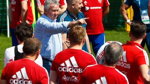 Former Russian national soccer coach Guus Hiddink, center, talks to players besides Russia head coach Stanislav Cherchesov during the official training session of the Russian team prior to the round of 16 match between Russia and Spain at the 2018 soccer World Cup at the Federal Sports Centre Novogorsk, near Moscow, Russia, Thursday, June 28, 2018. (AP Photo/Matthias Schrader)