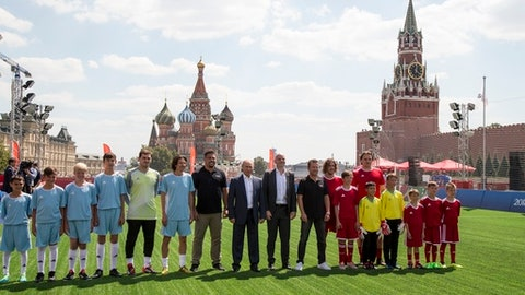 Russian President Vladimir Putin, center, and FIFA President Gianni Infantino, right of him, attend an opening friendly soccer match between two children teams and FIFA legends at a Football Park in Red Square during the 2018 soccer World Cup in the Spartak Stadium in Moscow, Russia, Thursday, June 28, 2018. (AP Photo/Alexander Zemlianichenko)