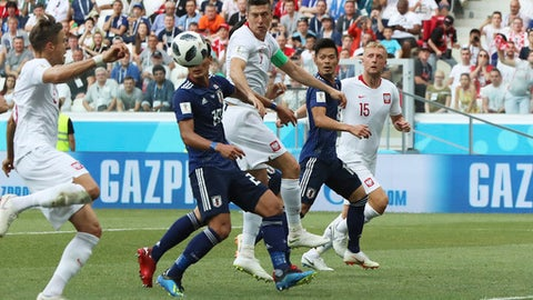 Poland's Jan Bednarek, left, scores his side's first goal during the group H match between Japan and Poland at the 2018 soccer World Cup at the Volgograd Arena in Volgograd, Russia, Thursday, June 28, 2018. (AP Photo/Eugene Hoshiko)