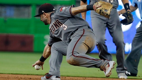 Arizona Diamondbacks second baseman Daniel Descalso (3) bobbles a ball hit by Miami Marlins' Derek Dietrich during the third inning of a baseball game, Thursday, June 28, 2018, in Miami. Descalso was charged with an error as Dietrich reached first base. (AP Photo/Wilfredo Lee)