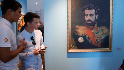 """FILE - In this Wednesday, June 20, 2018 file photo, visitors watch a portrait of Egypt's soccer star Mohamed Salah, part of the """"Like The Gods"""" exhibition, at the Museum of the Russian Academy of Arts in St. Petersburg, Russia. It's a collection of digitally made portraits of around 40 modern soccer superstars dressed in military and royal uniforms dating back to the 19th century. (AP Photo/Dmitri Lovetsky, File)"""