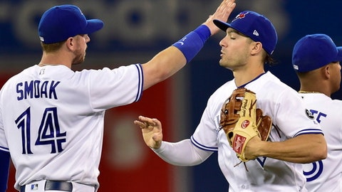Toronto Blue Jays' Justin Smoak (14) and Randal Grichuk (15) celebrate after the Blue Jays defeated the Detroit Tigers 3-2 in a baseball game Friday, June 29, 2018, in Toronto. (Frank Gunn/The Canadian Press via AP)