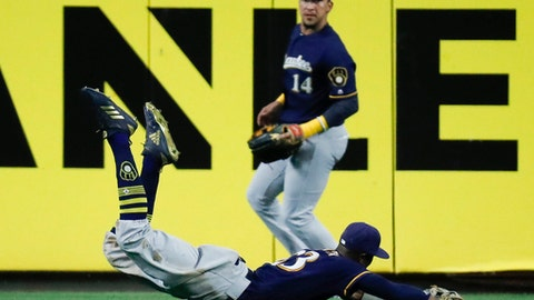 Milwaukee Brewers center fielder Keon Broxton, below, catches a fly ball by Cincinnati Reds' Scooter Gennett during the ninth inning of a baseball gam  Friday, June 29, 2018, in Cincinnati. (AP Photo/John Minchillo)