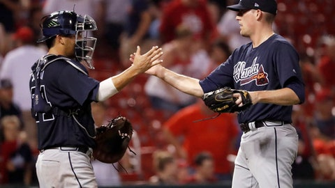 Atlanta Braves relief pitcher Dan Winkler, right, and catcher Kurt Suzuki celebrate following the team's 5-1 win in a baseball game against the St. Louis Cardinals on Friday, June 29, 2018, in St. Louis.  (AP Photo/Jeff Roberson)