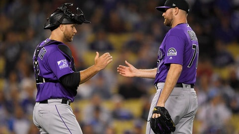 Colorado Rockies catcher Chris Iannetta, left, and relief pitcher Wade Davis congratulate each other after the Rockies defeated the Los Angeles Dodgers 3-1 in a baseball game Friday, June 29, 2018, in Los Angeles. (AP Photo/Mark J. Terrill)