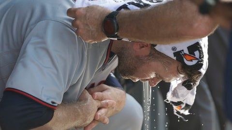 Minnesota Twins' Brian Dozier has a cold wet towel applied to his head during the seventh inning of a baseball game Chicago Cubs Saturday, June 30, 2018, in Chicago. Temperatures at Wrigley Field climbed into the mid 90's with a heat index over 100 degrees. (AP Photo/Charles Rex Arbogast)