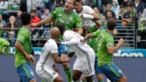 Seattle Sounders' Chad Marshall, center left, and Portland Timbers' Julio Cascante, center right, battle for a header in the first half of an MLS soccer match, Saturday, June 30, 2018, in Seattle. (AP Photo/Ted S. Warren)