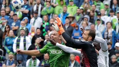 Portland Timbers goalkeeper Jeff Attinella, second from right, leaps to grab the ball in front of Timbers' Larrys Mabiala, right, and Seattle Sounders defender Chad Marshall, left, in the second half of an MLS soccer match, Saturday, June 30, 2018, in Seattle. The Timbers won 3-2. (AP Photo/Ted S. Warren)