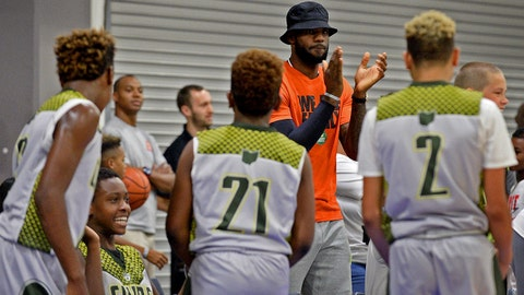 NBA star LeBron James, center/facing camera, encourages his son, LeBron Jr. and his teammates during youth tournament action at the Charlotte Convention Center in Charlotte, N.C., on Friday, July 21, 2017. (Jeff Siner/Charlotte Observer/TNS via Getty Images)
