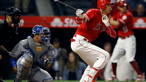 Los Angeles Angels' Shohei Ohtani, right, hits a single to right with Kansas City Royals catcher Salvador Perez and home plate umpire Gabe Morales, left, watching during the sixth inning of a baseball game in Anaheim, Calif., Monday, June 4, 2018. (AP Photo/Alex Gallardo)