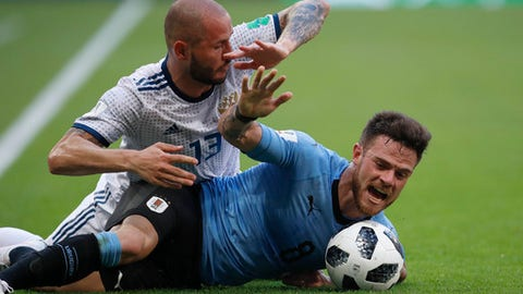 Russia's Fyodor Kudryashov, left, and Uruguay's Nahitan Nandez challenge for the ball during the group A match between Uruguay and Russia at the 2018 soccer World Cup at the Samara Arena in Samara, Russia, Monday, June 25, 2018. (AP Photo/Hassan Ammar)