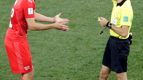 Referee Clement Turpin shows a yellow card to Switzerland's Fabian Schaer during the group E match between Switzerland and Costa Rica, at the 2018 soccer World Cup in the Nizhny Novgorod Stadium in Nizhny Novgorod , Russia, Wednesday, June 27, 2018. (AP Photo/Mark Baker)