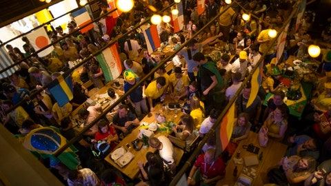 In this photo taken on Wednesday, June 27, 2018, soccer fans watch the soccer match between Serbia and Brazil in a pub in Nikolskaya street, near Red Square, during the 2018 soccer World Cup in Moscow, Russia. The World Cup is sending business surging across the 11 Russian cities hosting soccers biggest show. Bars, taxi services, dumpling sellers and nesting doll vendors are among those benefiting. The Russian president was counting on just such a boost after U.S. and European sanctions and low oil prices sank the country into recession. But experts warn the boon wont last long without deeper economic reforms.  (AP Photo/Alexander Zemlianichenko)