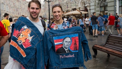 A Russian couple show jean jackets with a portrait of Russian President Vladimir Putin and words 'from Russia with love' to sell in the Nikolskaya street near the Kremlin during the 2018 soccer World Cup in Moscow, Russia, Saturday, June 30, 2018. (AP Photo/Alexander Zemlianichenko)