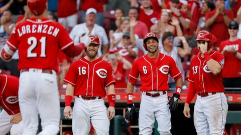 Cincinnati Reds' Michael Lorenzen (21) runs home to celebrate with Tucker Barnhart (16), Billy Hamilton (6), and Adam Duvall (23) after hitting a grand slam off Milwaukee Brewers relief pitcher Jacob Barnes in the seventh inning of a baseball game, Saturday, June 30, 2018, in Cincinnati. (AP Photo/John Minchillo)