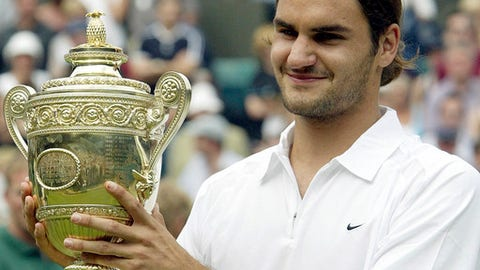FILE - In this July 6, 2003, file photo, Switzerland's Roger Federer holds the Men's Singles trophy after defeating Australia's Mark Philippoussis in the final of the All England Lawn Tennis Championships on the Centre Court at Wimbledon in London. Federer's paths to his record eight Wimbledon championships were each different, of course. Different opponents. Different degrees of difficulty. Same old Federer. (AP Photo/Dave Caulkin, File)