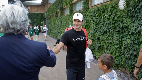 Roger Federer of Switzerland shakes hands with a well-wisher after a practice session ahead of the start of the Wimbledon Tennis Championships in London, Sunday, July 1, 2018. The Championships will start on Monday, July 2. (AP Photo/Ben Curtis)