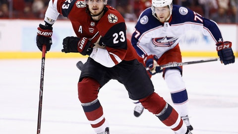 FILE - In this Jan. 25, 2018, file photo, Arizona Coyotes defenseman Oliver Ekman-Larsson (23) and Columbus Blue Jackets right wing Josh Anderson (77) skate to the puck during the first period of an NHL hockey game, in Glendale, Ariz. The Arizona Coyotes have signed All-Star defenseman Oliver Ekman-Larsson to an eight-year contract extension that averages $8.25 million per year. The contract, announced on Sunday, July 1, 2018, comes on the heels of a six-year, $33 million contract Ekman-Larsson signed in 2013. (AP Photo/Ross D. Franklin, File)