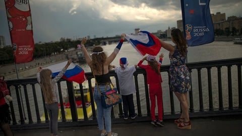 People wave Russian flags on the Krymsky Bridge to passengers aboard a ferry on the Moskva river in Moscow, Russia, Sunday, July 1, 2018. (AP Photo/Francisco Seco)