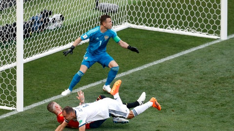 Russia's Sergei Ignashevich, front, scores an own goal during the round of 16 match between Spain and Russia at the 2018 soccer World Cup at the Luzhniki Stadium in Moscow, Russia, Sunday, July 1, 2018. (AP Photo/David Vincent)