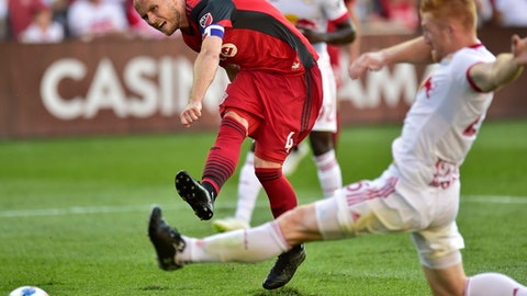 Toronto FC midfielder Michael Bradley (4) makes a shot on goal during second-half MLS soccer game action against the New York Red Bulls in Toronto, Sunday, July 1, 2018. (Frank Gunn/The Canadian Press via AP)