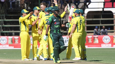 Australian cricket players celebrate the wicket of Pakistan batsman Muhammad Hafeez, center, as he walks off the pitch during the T20 cricket match at Harare Sports Club, Monday, July 2, 2018. Zimbabwe is playing host to a tri-nation series between Australia and Pakistan with all matches played as Twenty20 Internationals(AP Photo/Tsvangirayi Mukwazhi)
